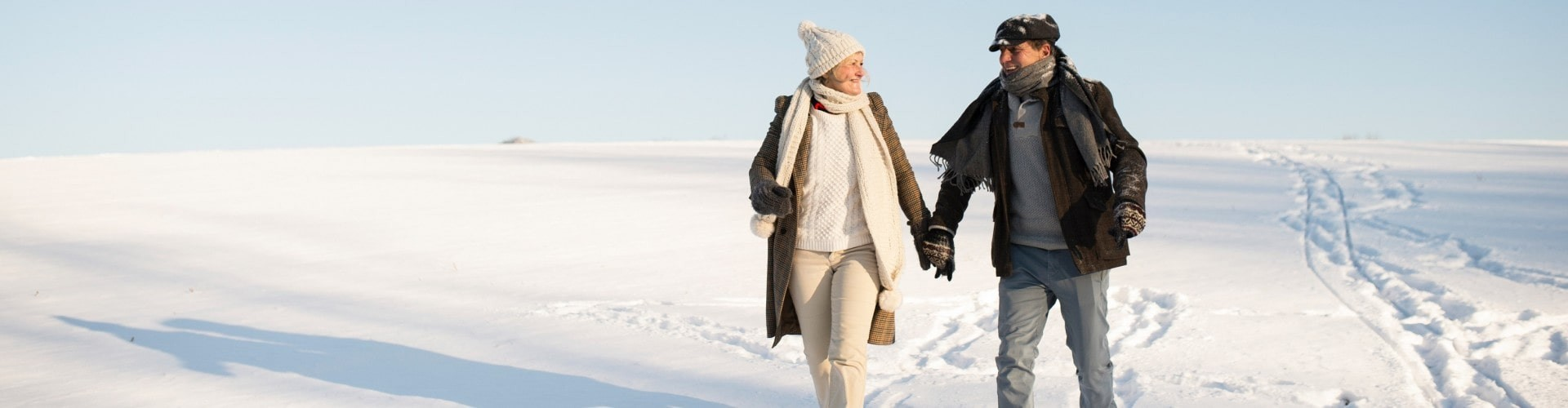 senior couple hiking through the snow