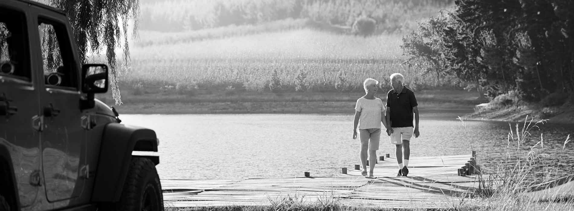 senior couple walking  on a lake dock towards their jeep